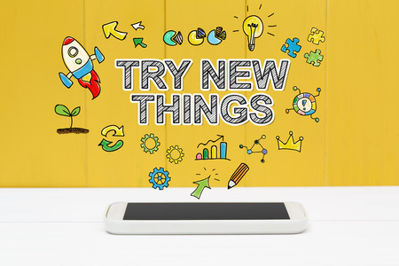 to try: Try New Things concept with smartphone on yellow wooden background Stock Photo
