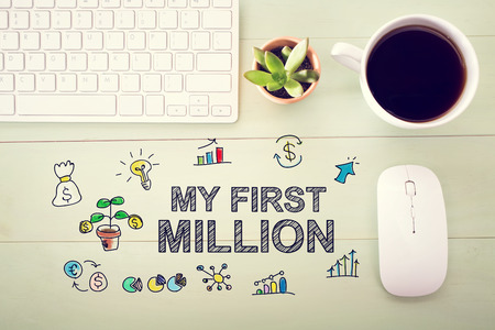 desk light: My First Million concept with workstation on a light green wooden desk Stock Photo