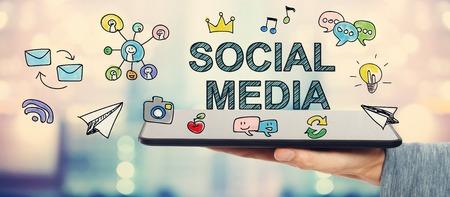 タブレット コンピューターを抱きかかえたとソーシャル メディアの概念