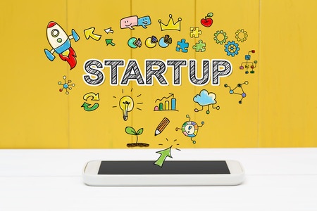 businesses: Start Up concept with smartphone on yellow wooden background