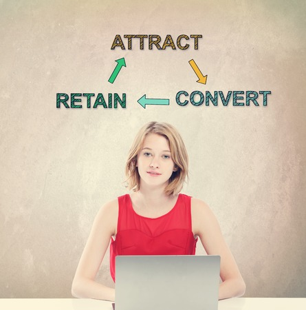convert: Attract, Retain and Convert concept with young woman working on a laptop Stock Photo