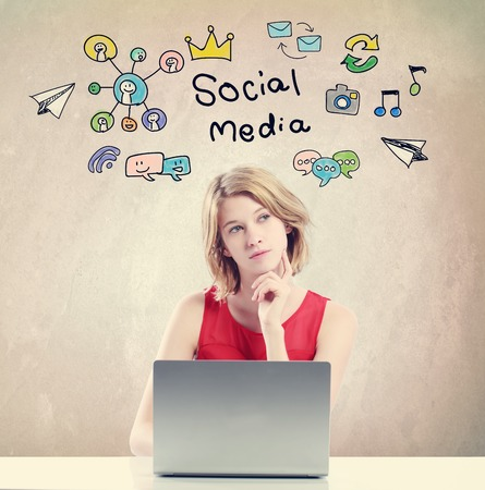 concept de médias sociaux avec jeune femme travaillant sur un ordinateur portable
