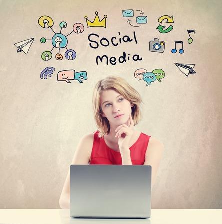 medios de comunicacion: del concepto de medios sociales con la mujer joven que trabaja en un ordenador portátil Foto de archivo