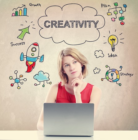 creativity concept: Creativity concept with young woman working on a laptop Stock Photo