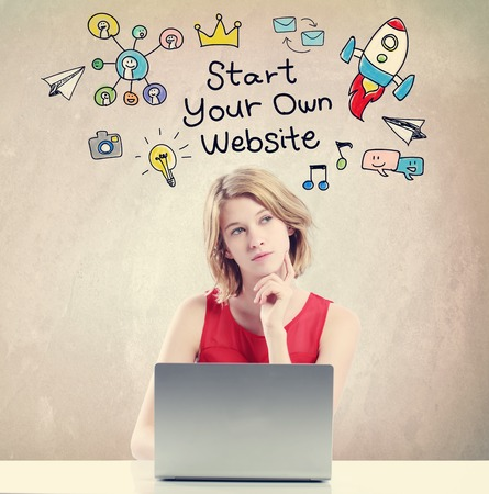 woman laptop: Start Your Own Website concept with young woman working on a laptop Stock Photo