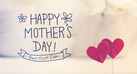 Mothers Day message with small red hearts with white dishes Stockfoto