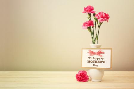 agradecimiento: Mensaje del día de madres con claveles de color rosa en un florero blanco