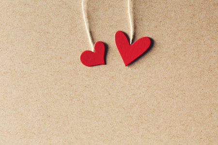 small paper: Handmade small paper hearts with strings on erthy colored paper background