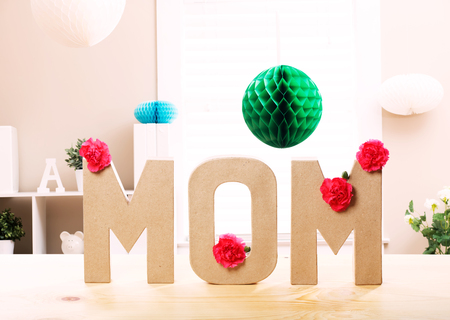 agradecimiento: Mom letter blocks with pink carnation flowers in a room