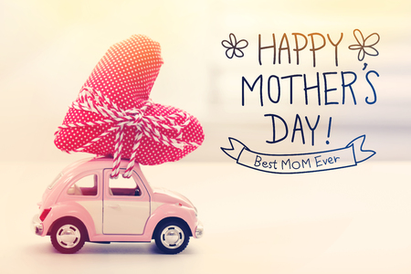 dia: Mensaje feliz del día de madres con un coche de color rosa miniatura que lleva un cojín de corazón Foto de archivo