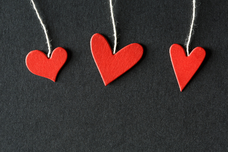 small paper: Handmade small paper hearts with strings on black paper background