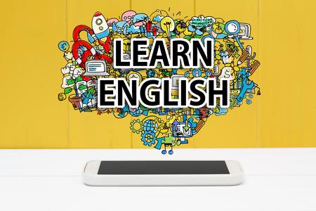 idiomas: Inglés aprender el concepto de teléfono inteligente en el fondo de madera de color amarillo