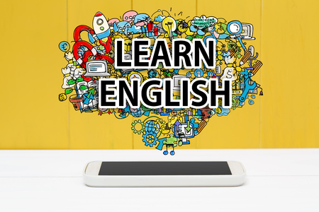 in english: Learn English concept with smartphone on yellow wooden background