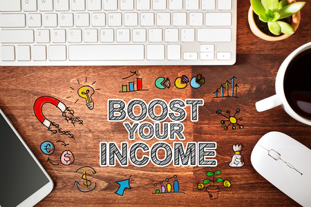 boost: Boost Your Income concept with workstation on a wooden desk