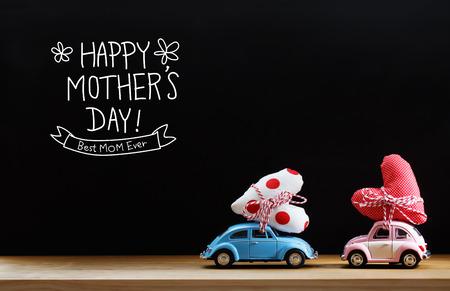 dia: mensaje del Día de la Madre con rosa y azul coches que llevan cojines del corazón
