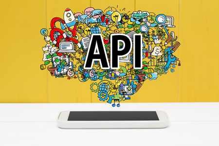 api: API concept with smartphone on yellow wooden background