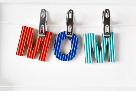 Colorful paper Mom letters hanging with clothespins