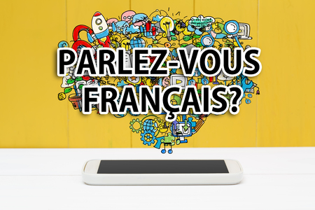 francais: Parlez Vous Francais concept with smartphone on yellow wooden background