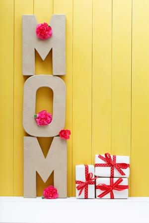 agradecimiento: bloques de la letra mamá con flores de clavel rosa sobre la pared de madera de color amarillo