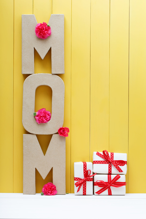 letter blocks: Mom letter blocks with pink carnation flowers over yellow wooden wall