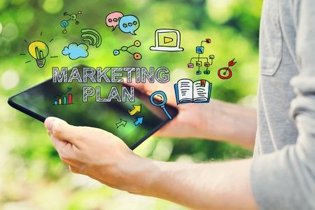 Concepto de plan de marketing con el hombre joven que sostiene su computadora de la tableta fuera en el parque