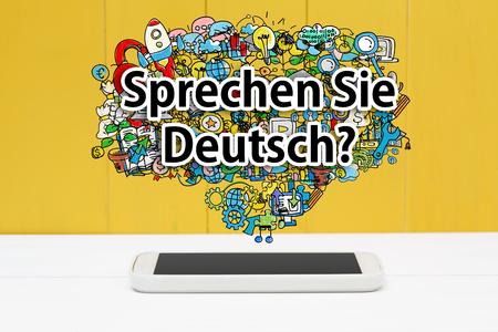 deutsch: Sprechen Sie Deutsch concept with smartphone on yellow wooden background