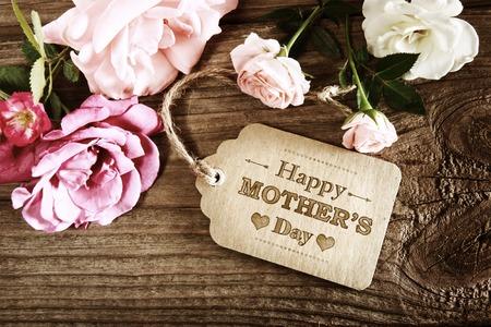 나무 테이블에 작은 핑크 장미와 어머니의 날 메시지
