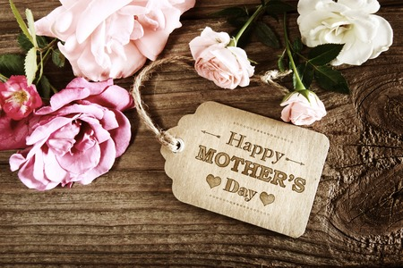 Mothers Day message with small pink roses on wooden table Stock Photo - 54371806