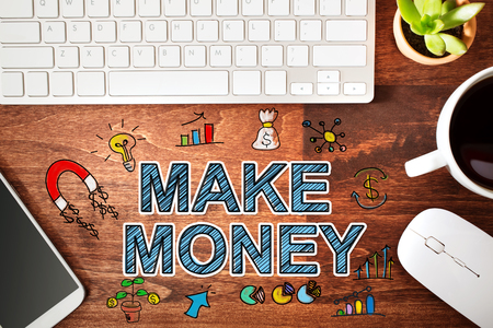Make Money concept with workstation on a wooden desk