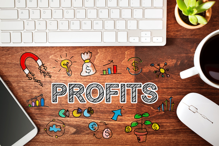 workstation: Profits concept with workstation on a wooden desk Stock Photo