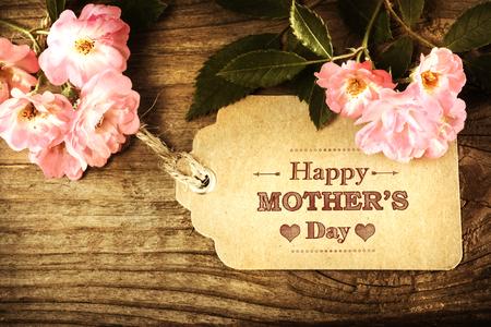 Las madres tarjeta del día con las rosas en el fondo de madera