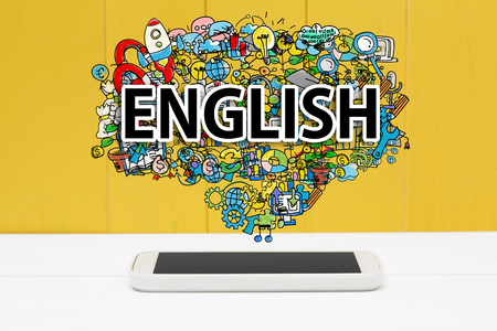 learning language: English concept with smartphone on yellow wooden background