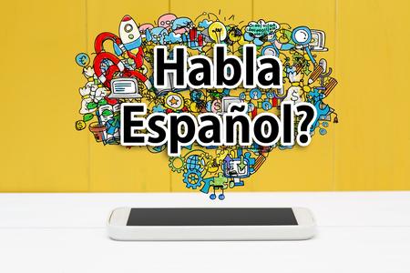 concetto parla spagnolo con lo smartphone su sfondo giallo in legno