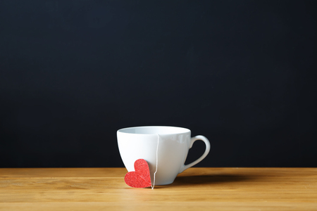 mothers day: Coffee cup with small red heart on black background