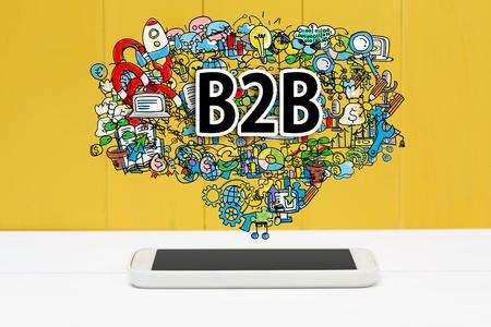 b2b: concepto B2B con el teléfono inteligente en el fondo de madera de color amarillo Foto de archivo