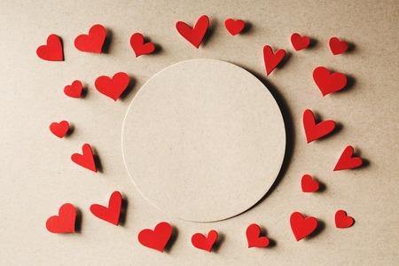 Handgemaakte kleine papieren harten met koorden op erthy gekleurd papier achtergrond Stockfoto