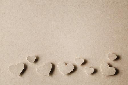 Handgeschept papier gesneden harten op erthy gekleurd papier achtergrond
