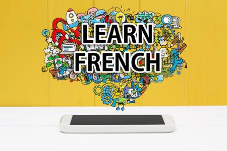 frances: Aprender concepto francés con el teléfono inteligente en el fondo de madera de color amarillo