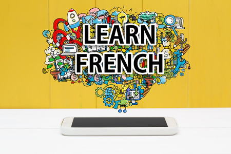 francais: Learn French concept with smartphone on yellow wooden background
