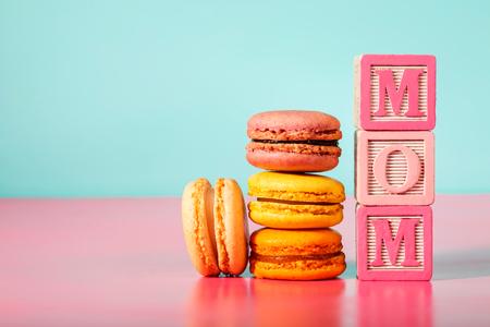 Macarons mit MOM-Nachricht auf Holzklötze auf Pastell rosa und blauen Hintergrund Standard-Bild - 54371547