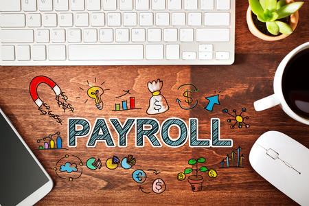payroll: Payroll concept with workstation on a wooden desk