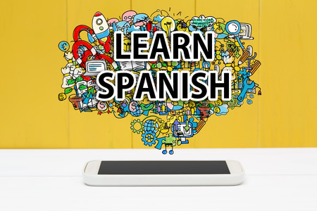 Learn Spanish concept with smartphone on yellow wooden background