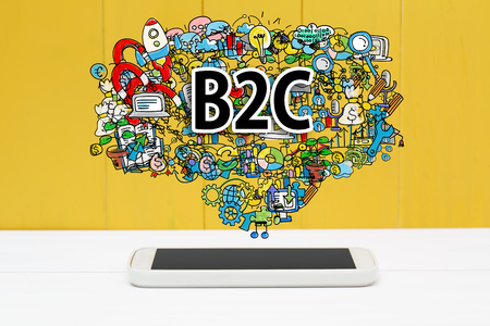 b2c: B2C concept with smartphone on yellow wooden background