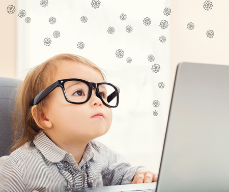 smart girl: Gears concept with toddler girl using her laptop Stock Photo