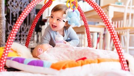 Muchacha feliz del niño que juega con su hermana recién nacida
