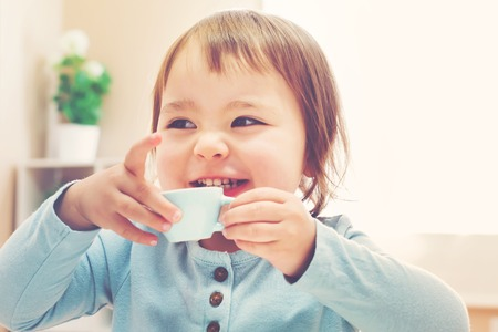 mixed race girl: Happy toddler girl drinking from a tiny teacup