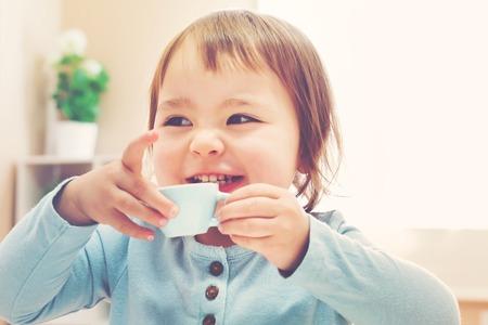 bebes niñas: Muchacha feliz del niño que bebe de una pequeña taza de té