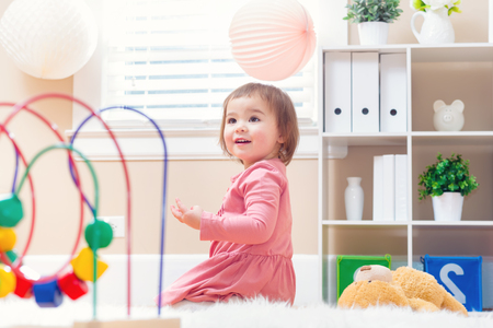 baby toys: Happy toddler girl playing with toys in her house