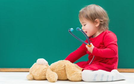 Happy toddler girl caring for her teddy bear with a stethoscope