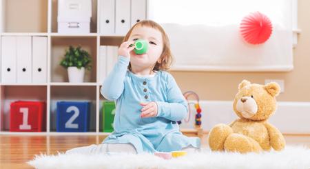 bebes niñas: Muchacha feliz del niño tiene el té con su oso de peluche Foto de archivo